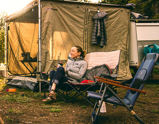 Woman smiling and relaxing in a camping chair, sitting next to another chair.