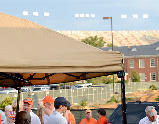Canopy with tan top during a tailgate.