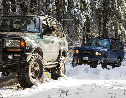 Two vehicles adventuring through the snow.
