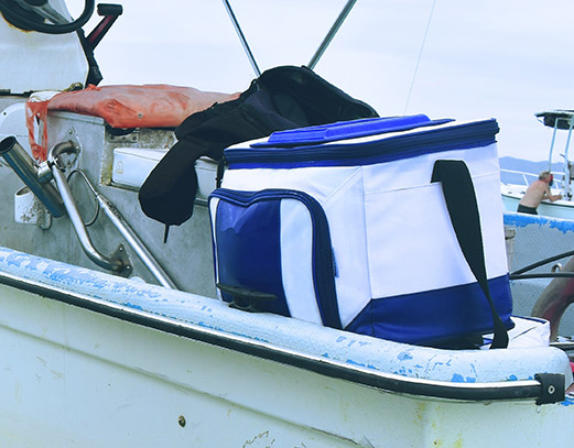Cooler sitting on the ege of a boat.